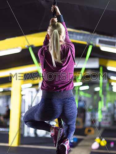 young muscular woman doing rope climbing in crossfitness gym