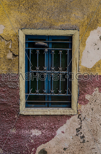 A blue window on a half yellow and half in red wall