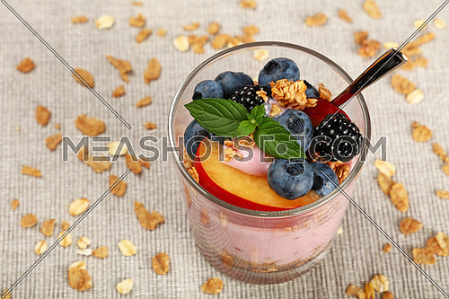 Close up portion of muesli granola breakfast with yogurt in glass, fruits and berries, high angle view