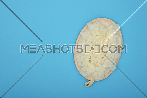 Close up one feminine soft bath shower skin scrub puff over blue background, elevated top view, directly above