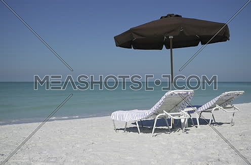 two sun beds and umbrella by the beach