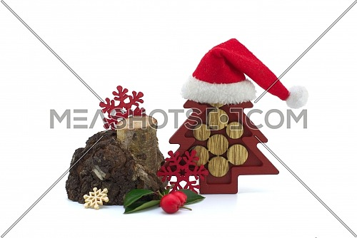 Christmas decorations composition with natural wooden stump, decorative snowflakes and Santa hat over small brown wooden Christmas tree, isolated on white background