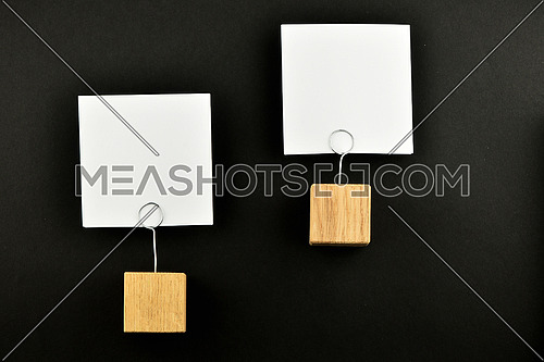 Two white paper notes at different levels with wooden holders isolated at black paper background for presentation