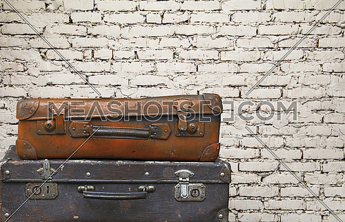 Close up stack of two old vintage antique grunge travel luggage brown leather suitcase trunks isolated over background of white brick wall, low angle side view