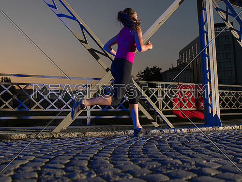 urban sports, young healthy woman jogging across the bridge in the city at early morning in night
