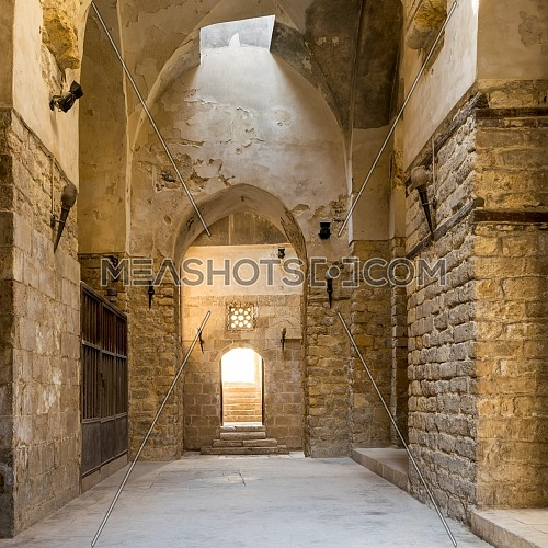 Interior of corridor of ancient building with arched doorways and shabby stone bricks walls
