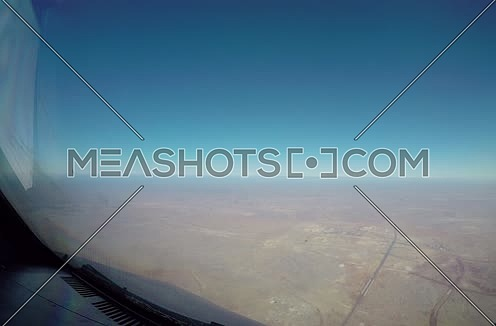 Close shot from inside plane cockpit showing sky horizon from the window and desert at day