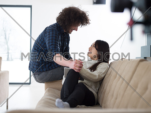 Young multiethnic couple relaxing at luxury home with tablet computers reading in the living room on the sofa couch.