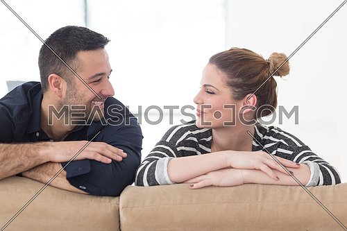 Portrait of young couple sitting on sofa in modern white apartment