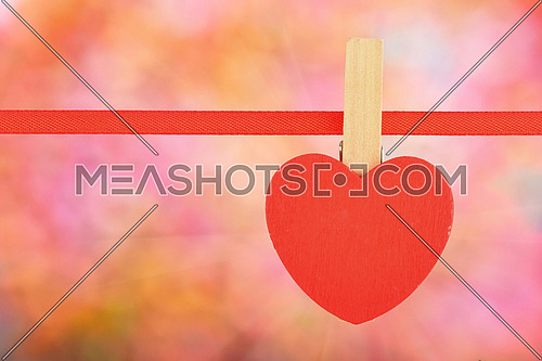 Valentine day template, one red wooden heart with clothes pin on textile ribbon over bright colorful glitter blur