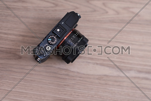 black camera on a wooden table top view