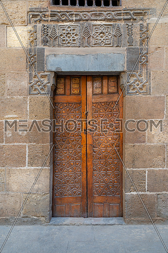 Wooden ornate door with geometrical engraved patterns on external old decorated bricks stone wall leading to Beit (house) Al Sehemy historical house, Cairo, Egypt