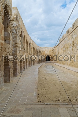 Stone bricks wall with embedded recessed arches at an old abandoned horse stall attached to the Citadel of Qaitbay, Alexandria, Egypt