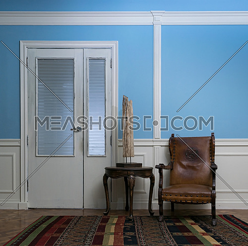 Leather armchair and wooden table lamp on round coffee table on background of blue wall, vintage door, wooden floor and colorful carpet
