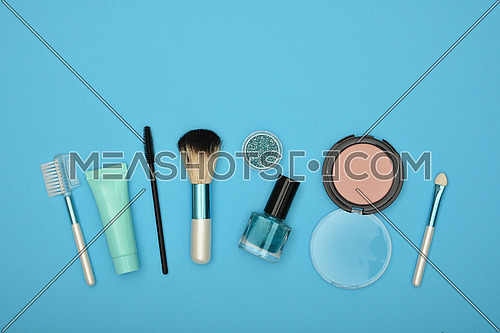 Feminine beauty care flat lay of face makeup blush, brushes, nail polish and glitter over blue background, elevated top view, directly above