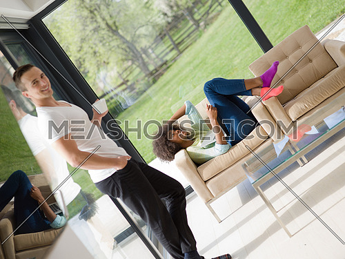 Young multiethnic couple relaxing at luxurious home with laptop computers reading in the living room on the sofa couch.