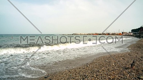 Ligurian beach formed by pebbles, seen from below where the waves break on the pebble beach, Varazze, Liguria Italy.
