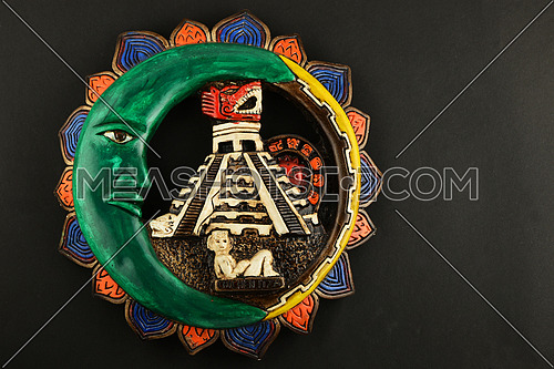 Mexican Mayan Chichen Itza souvenir ceramic painted plate with Moon, pyramid and girl isolated on black paper
