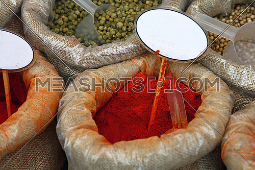 Close up several canvas bags of assorted spices, red paprika, green peppercorns, with copy space of blank price tags on retail display of market stall, high angle view