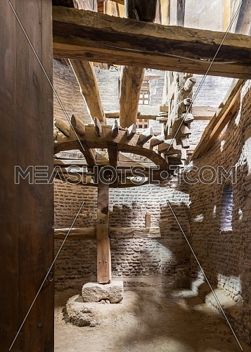 Open grunge door revealing aged water mill turning inside weathered mill building at Amir Taz palace, Medieval Cairo, Egypt