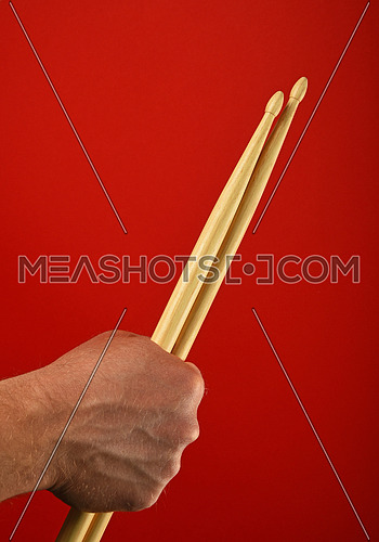 Man hand holding two wooden drumsticks over red background, close up