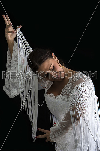 Flamenco dancer dressed in white with expression of feeling passionate in black background