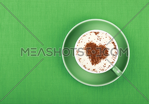 Close up one latte cappuccino coffee with heart shaped chocolate milk topping in red cup with saucer over background of green tablecloth, elevated top view, directly above