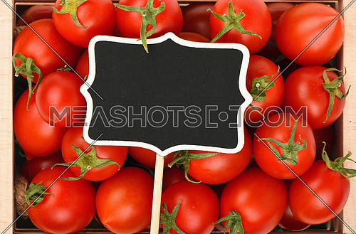 Red ripe fresh small cherry tomatoes in wooden box with black chalkboard price sign tag close up