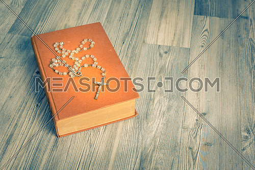 vintage rosary beads on old books, view above.