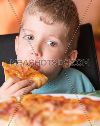 Beautiful happy young boy biting off slice of fresh made pizza,She sit at black chair, He has blonde hair.