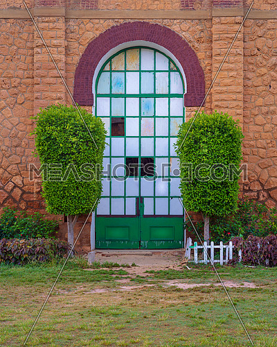 Closed grunge door with green metal grid framed by two green bushes in orange colored bricks stone wall in sunrise time at Montaza public park, Alexandria, Egypt