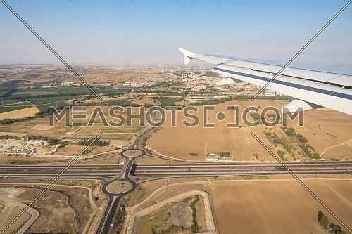 Ariel Shot through aircraft window during the flight. Aircraft wing over blue skies, crossroads and cityscape background