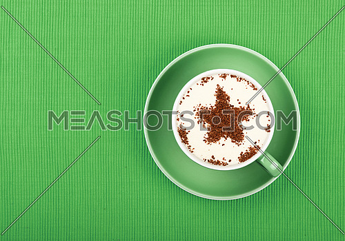 Close up one latte cappuccino coffee with star shaped chocolate milk topping in red cup with saucer over background of green tablecloth, elevated top view, directly above