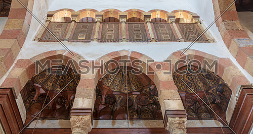 Three arches revealing three wooden domes decorated with floral patterns with interleaved wood window (Mashrabiya) located at the Mamluk era Beshtak Palace, Cairo, Egypt