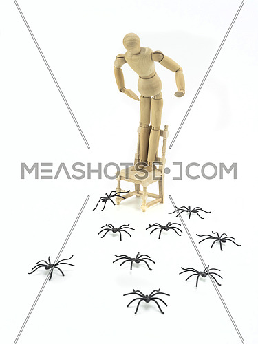 Wooden doll uploaded to chair with spider phobia, conceptual image
