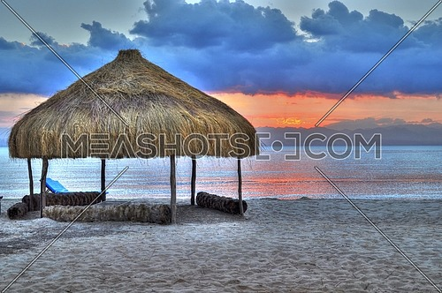 A beach tent made of natural wood and palm trunks during sunset