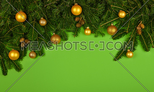 Close up fresh spruce or pine Christmas tree branches decorated with cones, golden balls and baubles, over green background with copy space