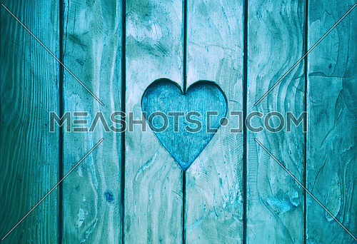 Close up one heart shape, symbol of love and romance, wood carved in blue painted wooden window shutter