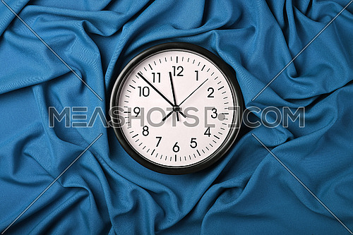 Close up white wall classic clock over blue textile background with folded pleats of fabric, elevated top view, directly above