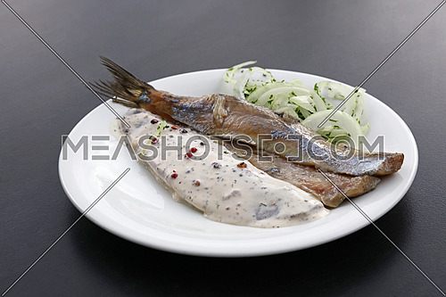 Close up portion of salted pickled herring fish filets with onions and sauce on white plate over black table, high angle view