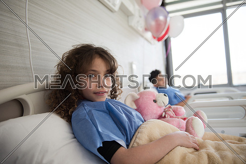 young middle eastern girl lies in a hospital bed while hugs pink teddy bear