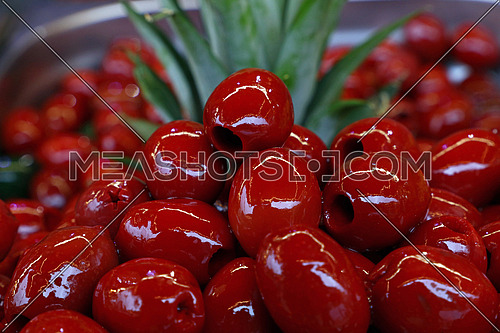 Red pitted glossy Italian Cerignola olives in oil close up over green pineapple leaves, retail market stall display, low angle view