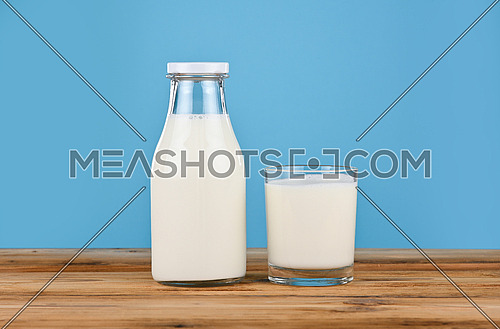 Close up one bottle and one drinking glass full of fresh milk on wooden table over blue background, low angle, side view