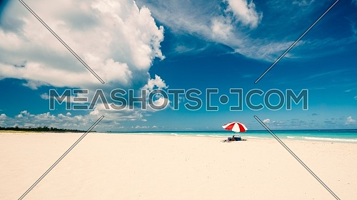 Awesome beach of Varadero during a sunny day, fine white sand and turquoise and green Caribbean sea,on the right one red parasol,Cuba.concept photo,copy space,vintage style.