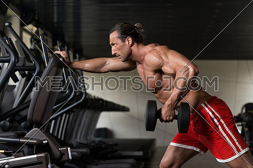 Muscular Mature Man Doing Heavy Weight Exercise For Back With Dumbbell In Modern Fitness Center