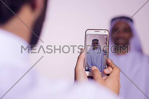 middle eastern business man taking portrait photos with phone