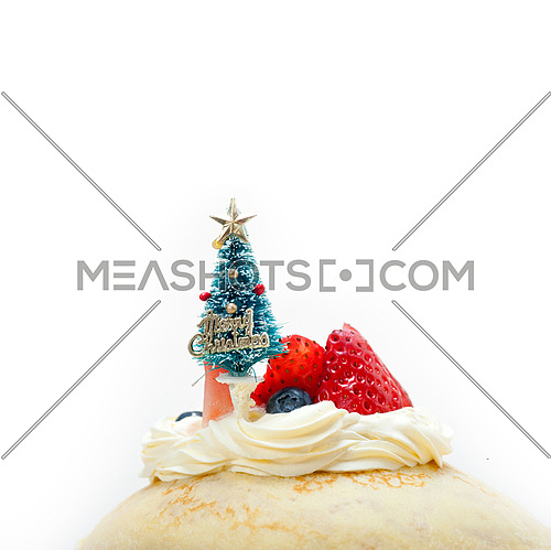 christmas tree on top of a pancake crepe mountain with whipped cream and strawberry