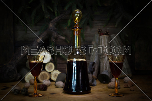 Red Wine Vintage Bottle and Glasses Resting On Wooden Table Against Christmas Background With Wood logs and Pine Branches