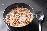 Pouring cereal flakes and milk