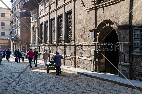 Cairo, Egypt- December 19 2015: Moez Street with local visitors and facade of Ottoman era historic Soliman Agha El Silahdar complex building, Old Cairo